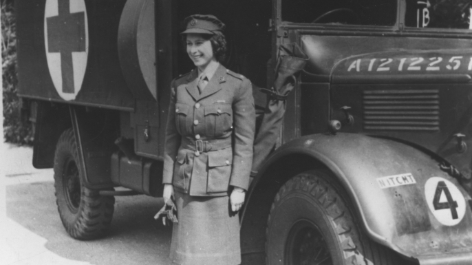 Elizabeth wears an officer's uniform and stands beside an Auxiliary Territorial Service first aid truck during World War II. (Credit: Keystone/Getty Images)